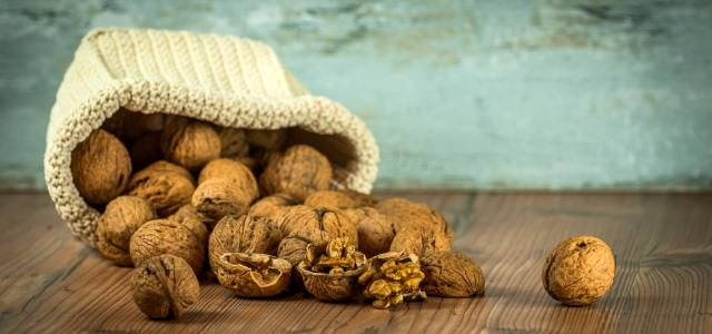 Small sack of walnuts on a wooden floor